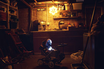 Basement workshop filled with tools, laundray basket, and an antique baby strioller lit with one lightbulb.