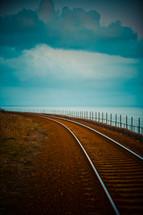 A train track curving along an ocean shore.