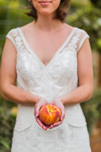woman in white dress holding a peach