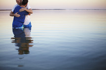 Two men embrace after being Baptized