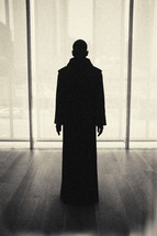 dark silhouette - priestly figure standing - window