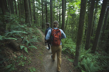 men backpacking through a forest