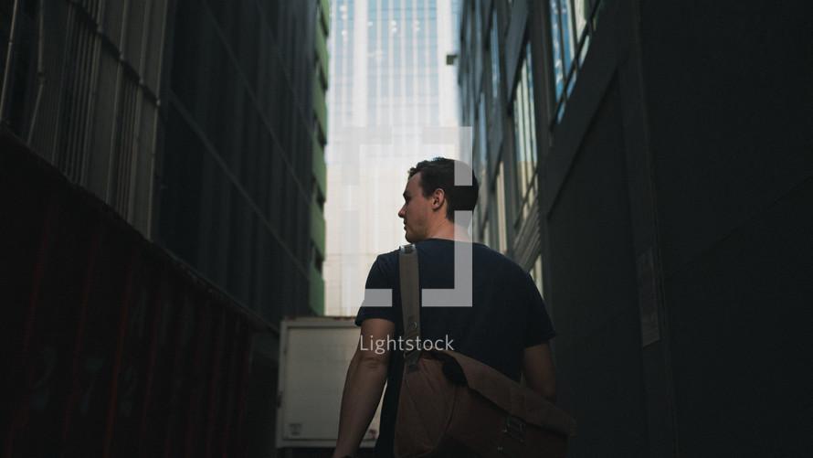 a man with a satchel walking through a city