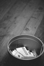 bucket with cash and envelopes for offering