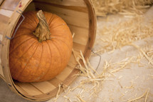 Pumpkin sitting in tilted basket surrounded by hay.
