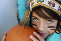 A child in a costume, holding a pumpkin.