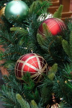Red, gold and green ball Christmas ornaments with pine branch.