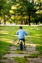 Little boy riding bike in park