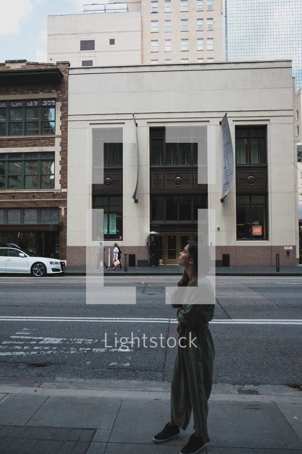 a woman standing on a downtown sidewalk looking up
