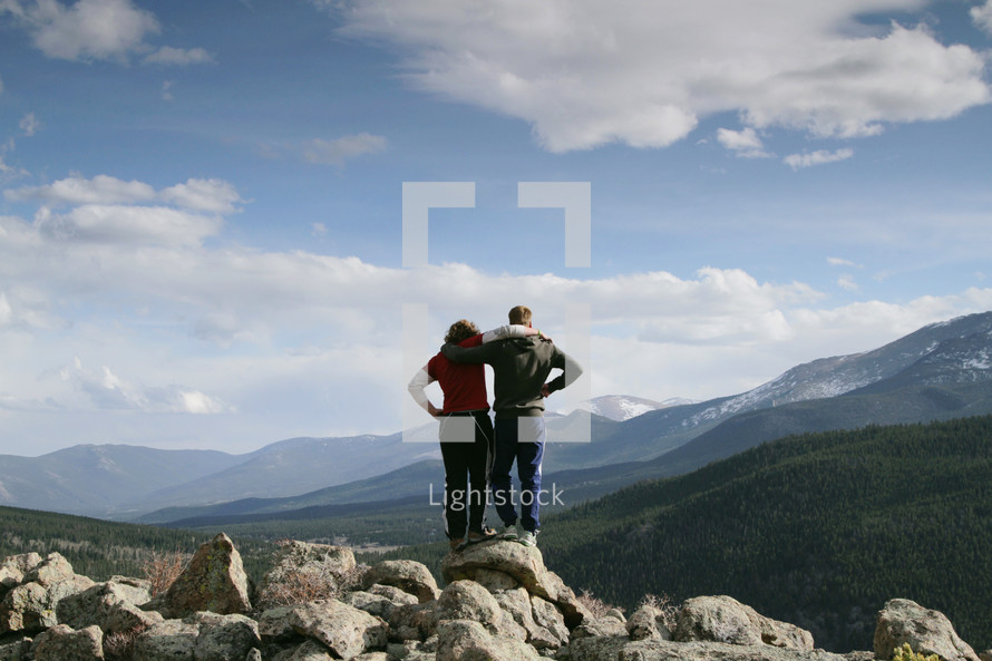Embraced couple standing on rocks near a mountain range.