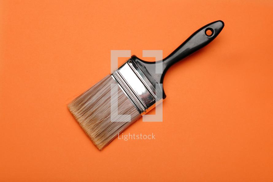 Paintbrush on an orange background.