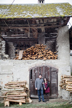 a couple standing in front of an old wood mill