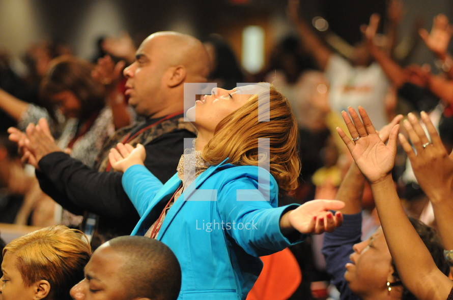 Congregation with arms raised praising God at worship service.