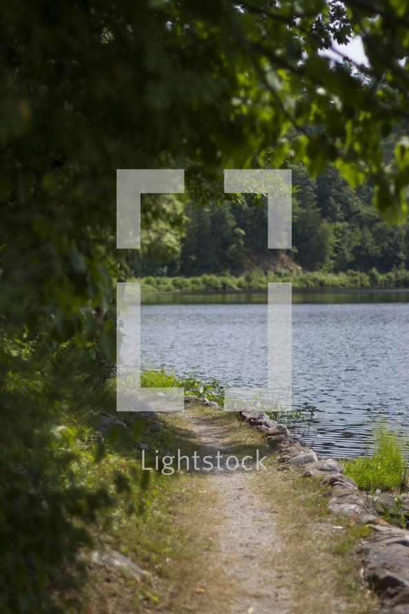 A view down a stone path along a lake.