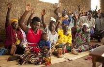 A group of Ugandan women lift their hands in prayer