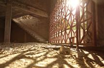 sun shining through lattice windows onto a dirt floor room