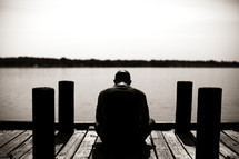 A man sitting on a dock praying