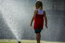 Child playing in the water sprinklers.
