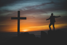 silhouette of a man and cross at sunset