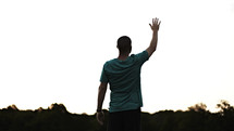A young adult man lifting his hand in worship