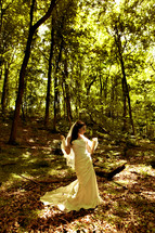 Bride standing in a forest in her gown