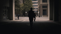 silhouettes of people walking on a city street