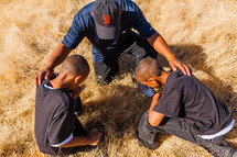 father and sons kneeling in prayer in a field african american laying hands