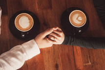 a couple holding hands over coffee