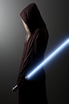 Jedi Guardian; woman in brown robe holding a blue lightsaber.