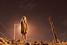 woman standing on rocky soil in front of a street light