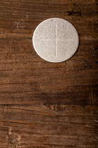 A single communion wafer on a wooden surface.