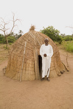 African man standing in front of a grass hut in a rural setting