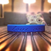 Blue Love On bracelet sitting on wood slat table with lights and pillows in the background.