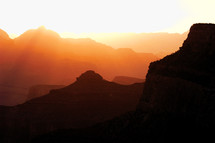 Sun shines in through haze over a mountain range.