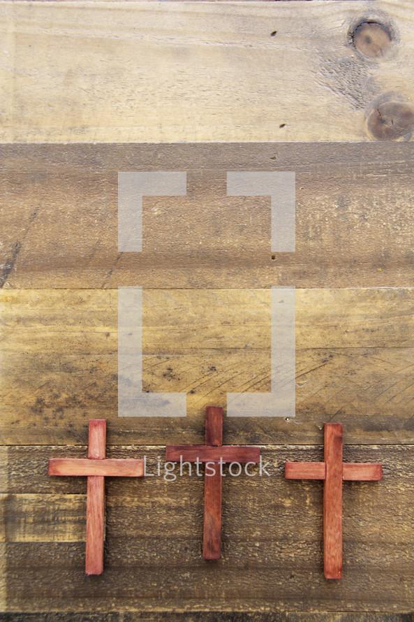 three wooden crosses on a wood floor