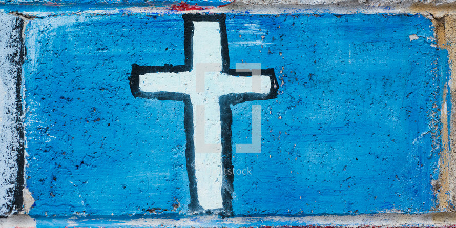 A primitive painting of a white cross on a blue background.