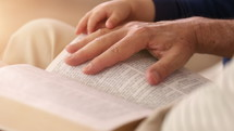 toddler hand on a father's hand as he reads the Bible