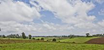 Farm land below billowing clouds