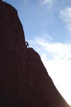 Man climbing steep mountain side