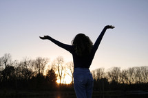 silhouette of a woman with hands raised