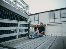 couple sitting on a wooden ramp