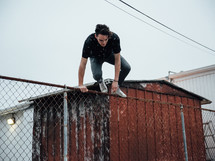 a man climbing over a chain linked fence
