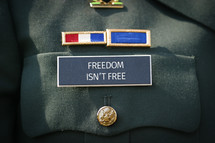 Freedom isn't free printed on the military name badge of uniform.