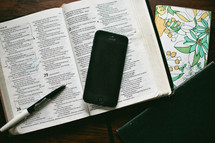 open Bible, pen, journal, and cellphone
