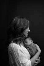 A mother holding a newborn close