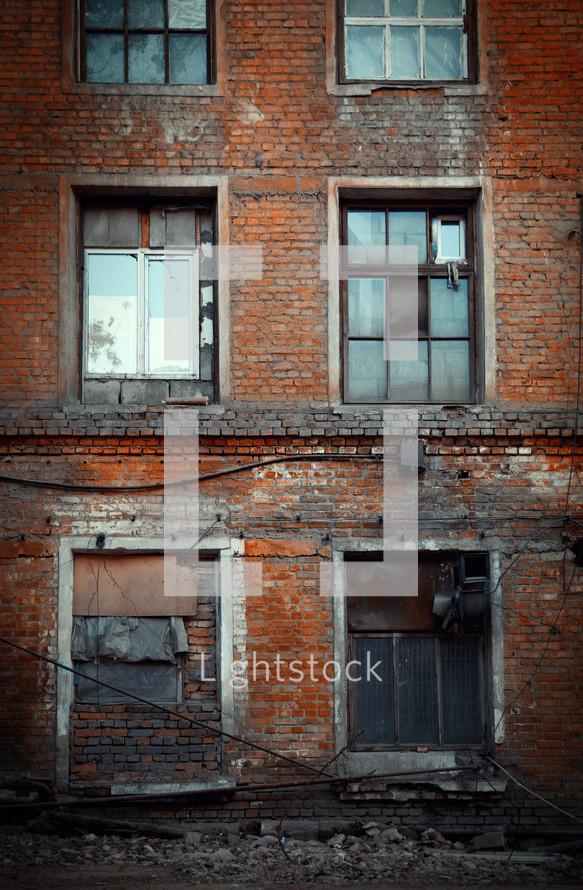 broken windows on an abandoned brick building
