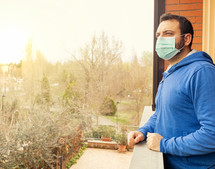 caucasian man with mask looking out on the terrace of the house during the quarantine due to the pandemic of covid19 coronavirus.