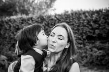 A little boy kissing a woman on the cheek