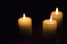 Three white candles with flame.