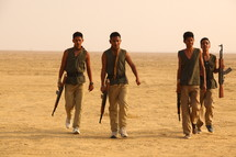 young men walking with rifles through the desert
